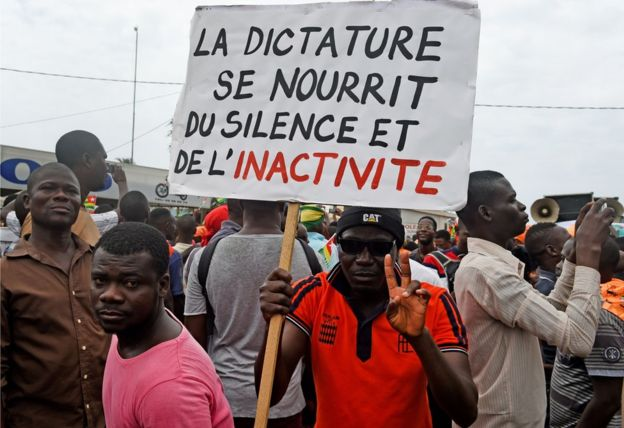 A protestor holds up a sign exhorting opposition against dictatorship in Togo (West - Africa) in 2017